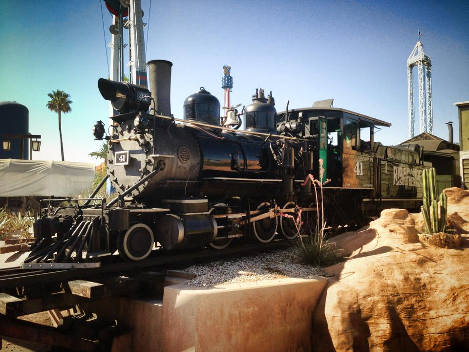 Steam locomotive passes small cactus and themed rock work.