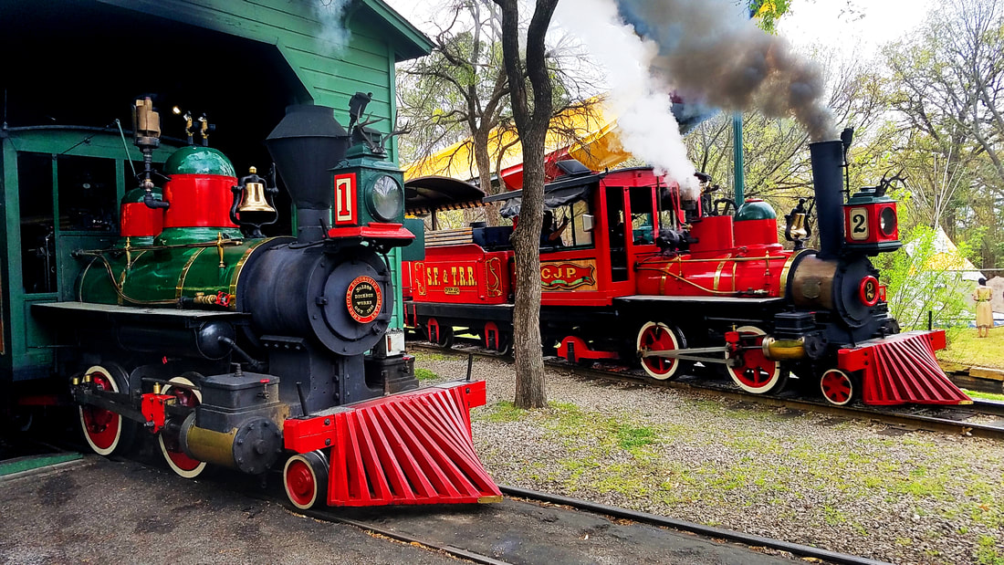 Two Steam locomotives. On the left, a green locomotive with a 1 sits in an engine house. On the right, a red locomotive with a