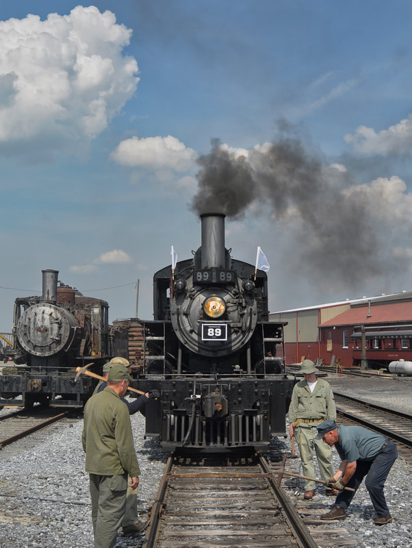 Steam locomotive with #89 and white flags with smoke sits next to an old unused locomotive in a rail yard as a track crew works on the rails with large hammers.