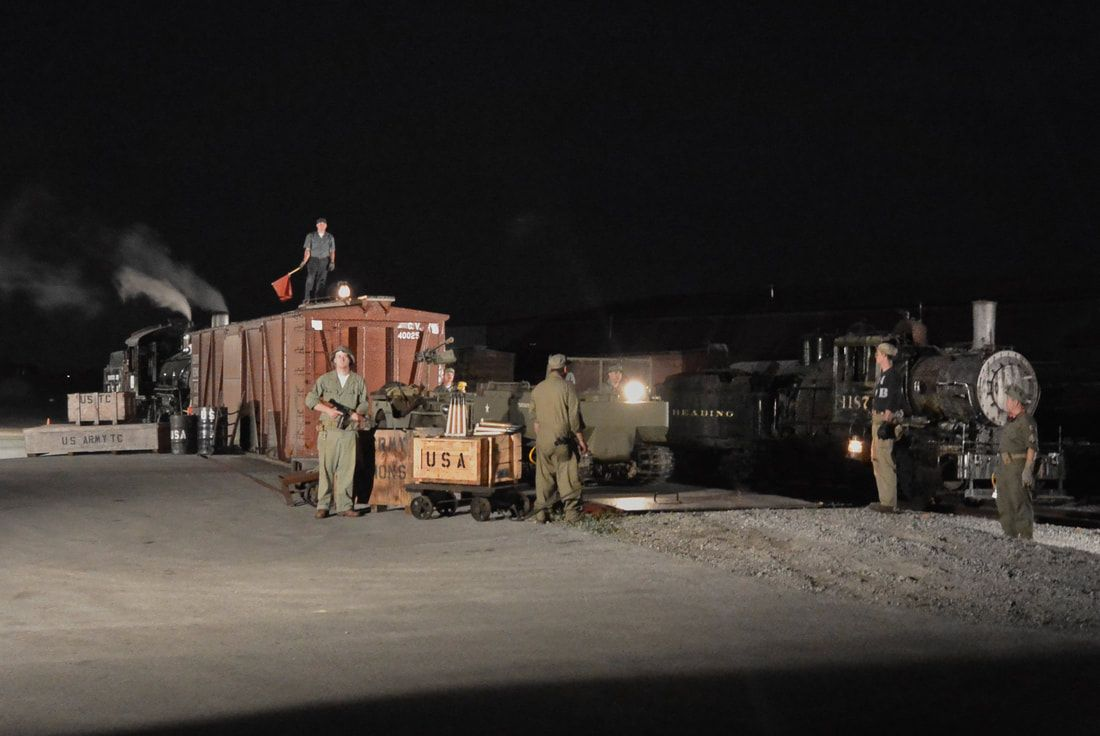 Night Photography with steam locomotives and a box car in a rail yard with WWII era actors posing with US Army props.