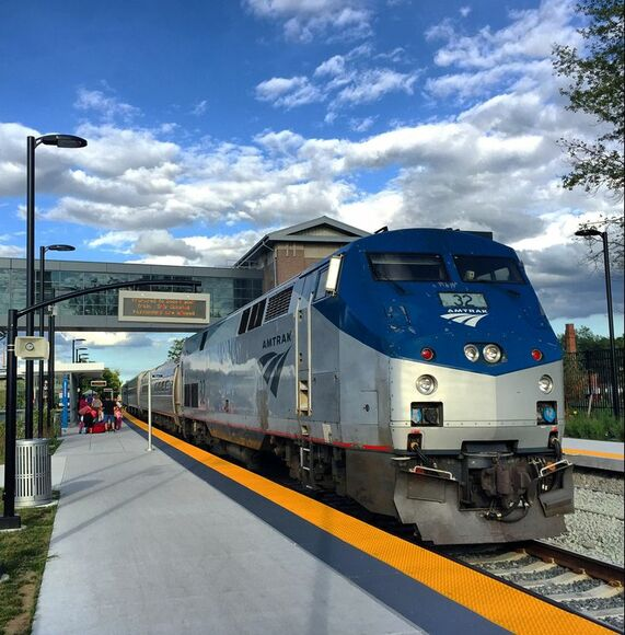 Front of Amtrak train arriving on a platform. #32 is on the front of the Silver and Dark Blue diesel locomotive. Glass walkway with information sign is above the train.