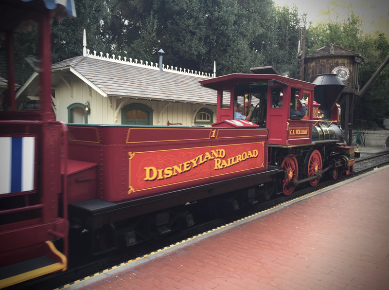 "Side view of steam locomotive arriving at station platform. ""Disneyland Railroad"" written on the tender."