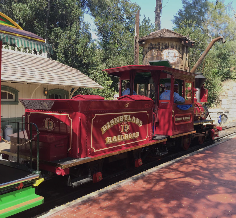 "Side of Steam Locomotive arriving on platform with wood water tower and a depot in the background. ""Disneyland Railroad 4"" is written on the tender."