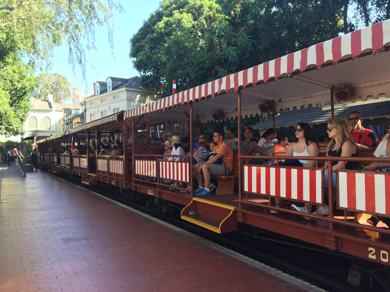 Disneyland Passenger train at brick platform. Brown train cars with steps in the middle. Red and White Stripes on roof and sides.