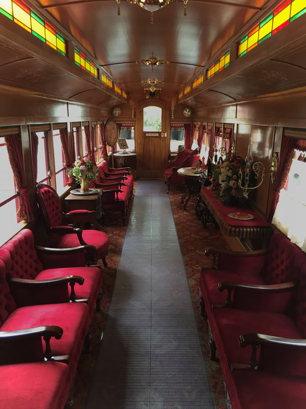 Interior of victorian decorated passenger railcar. Red plush seating, flower vases, and stained glass.
