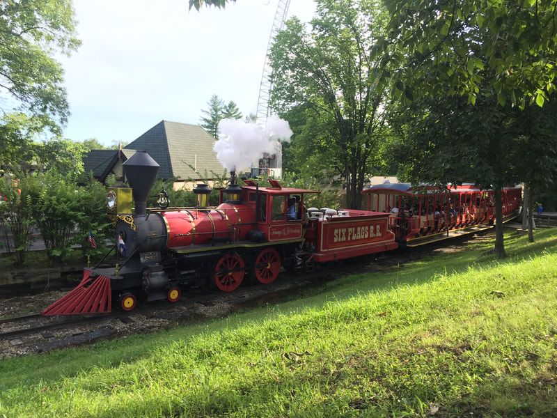"Red Steam Locomotive lets off steam as it pulls train. ""Six Flags RR"" is written on Tender."
